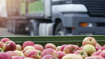 Container of apples with a lorry in the background